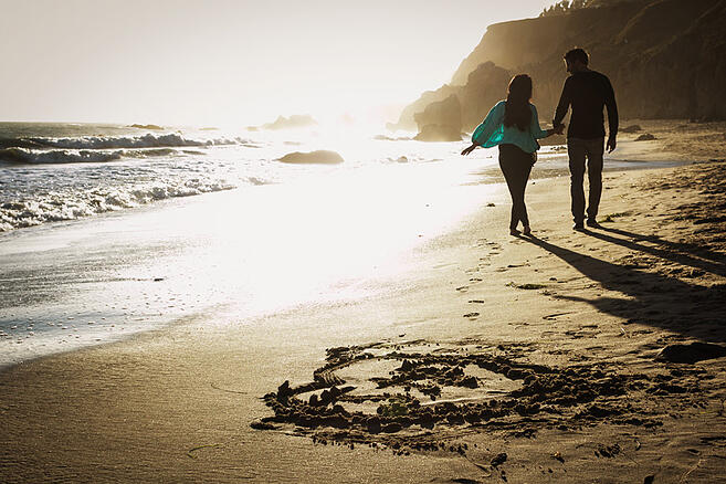 Jenn and Peter hold hands as they walk together on the beach